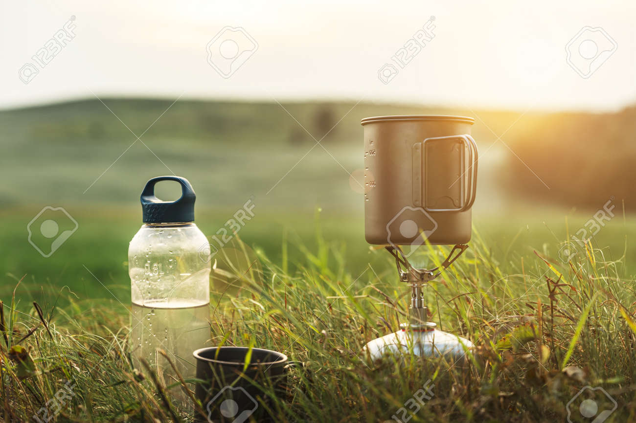 Camping gas burner outdoors on a sunset background. Cooking food during the hike. Adventure, travel, tourism and camping concept. - 151872197