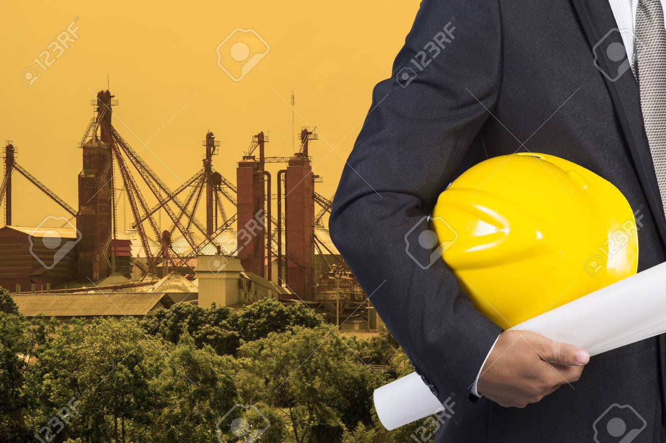 Engineer hand holding yellow helmet for workers security and stock engineer hand holding yellow helmet for workers security and blueprint paper plan against the background of malvernweather Choice Image