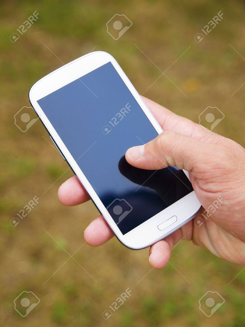 Man hand touching screen on modern mobile smart phone on natural green background - 15224073