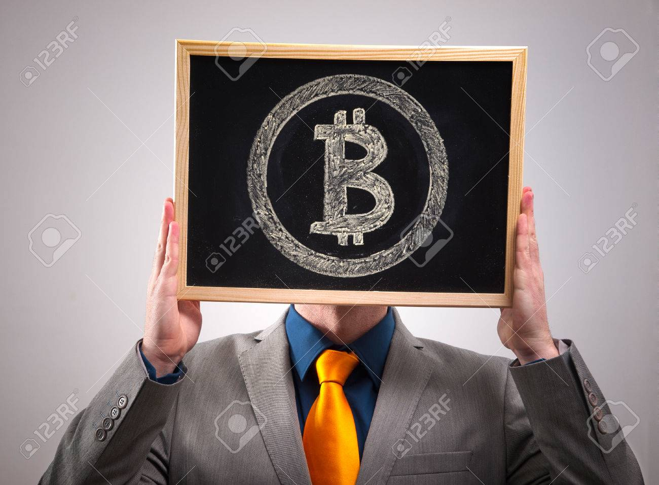 Businessman hiding his face behind bitcoin symbol and isolated on dark background - 26045534