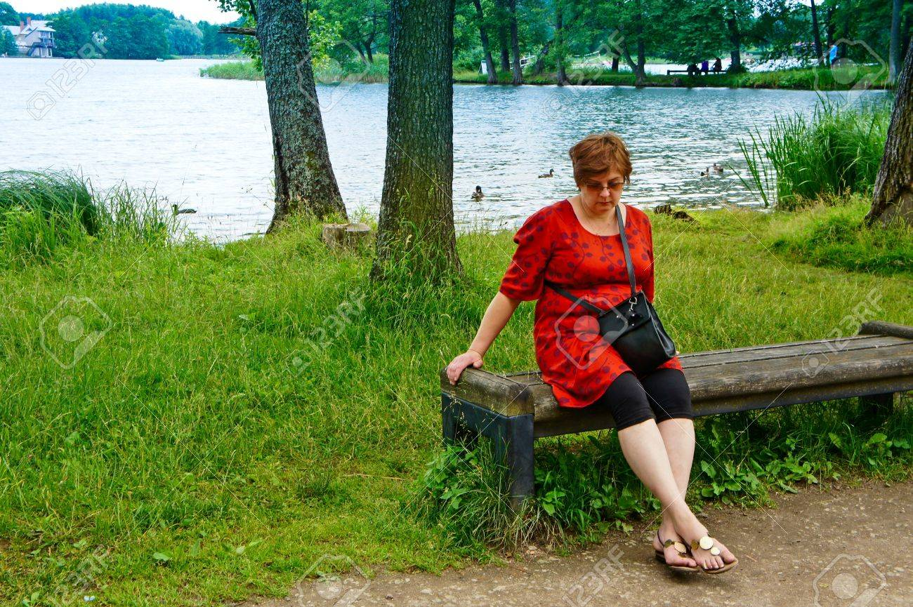 Mature Woman Looking Sad And Tired Sitting On A Park Bench Stock