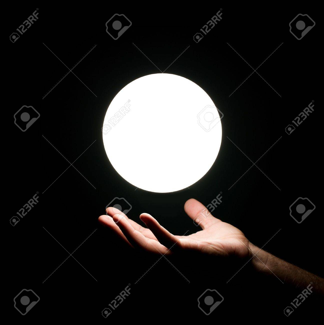 Bright light ball over human hand isolated on black background Stock Photo - 14743762