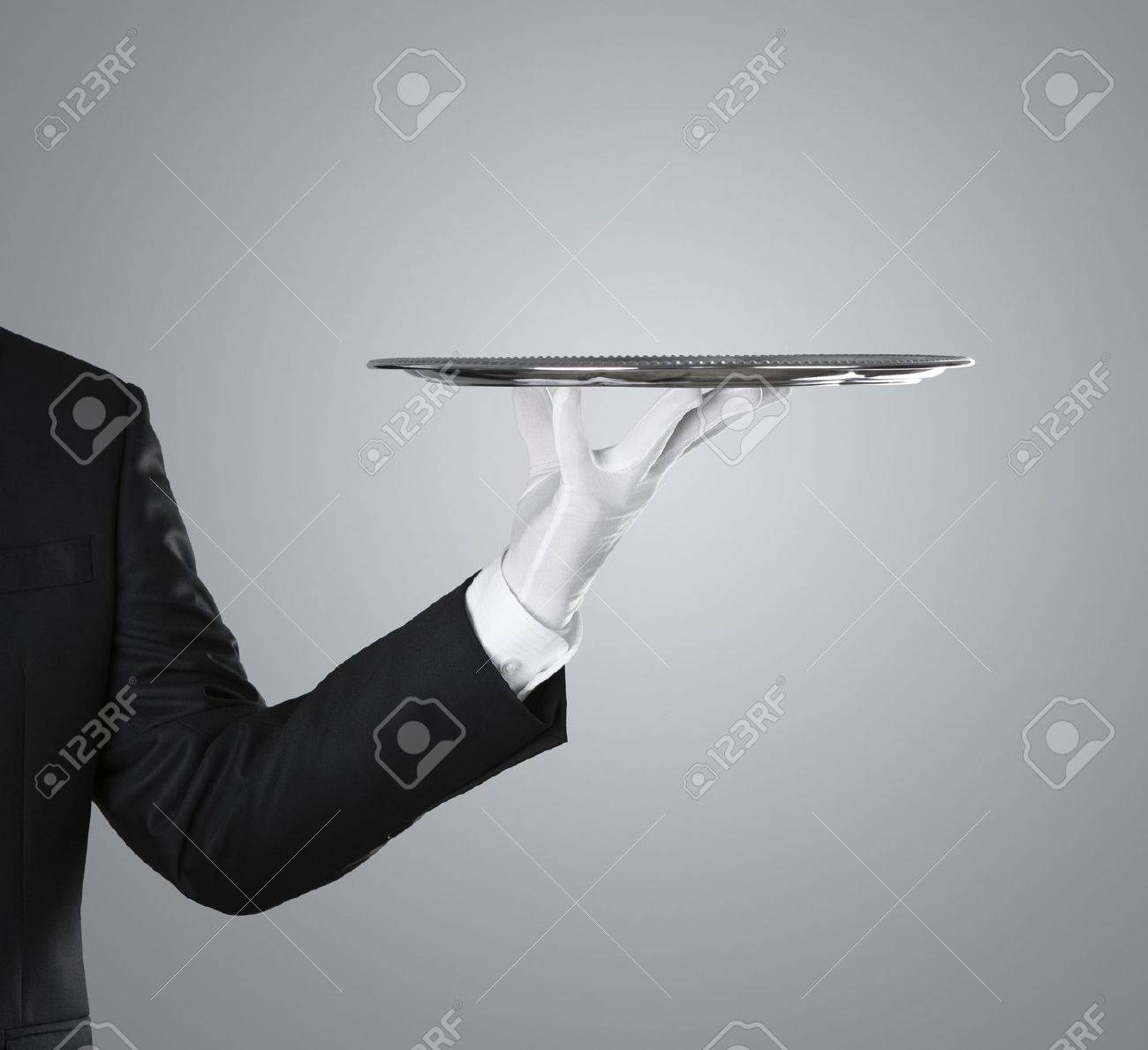 Waiter holding empty silver tray over gray background with copy space - 15437576