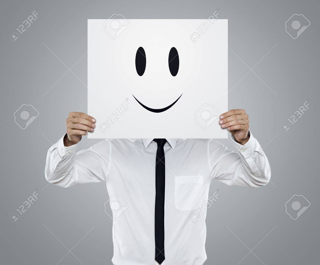 Young businessman holding card with a happy face on it isolated on gray background Stock Photo - 16398905