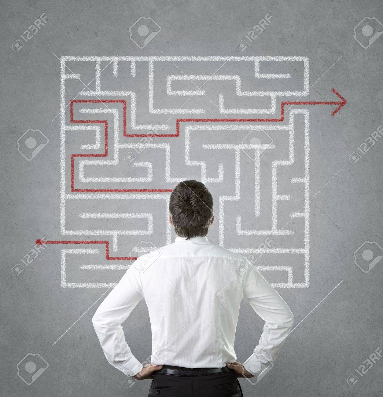 Confused young businessman looking at the labyrinth on the wall - 17662579