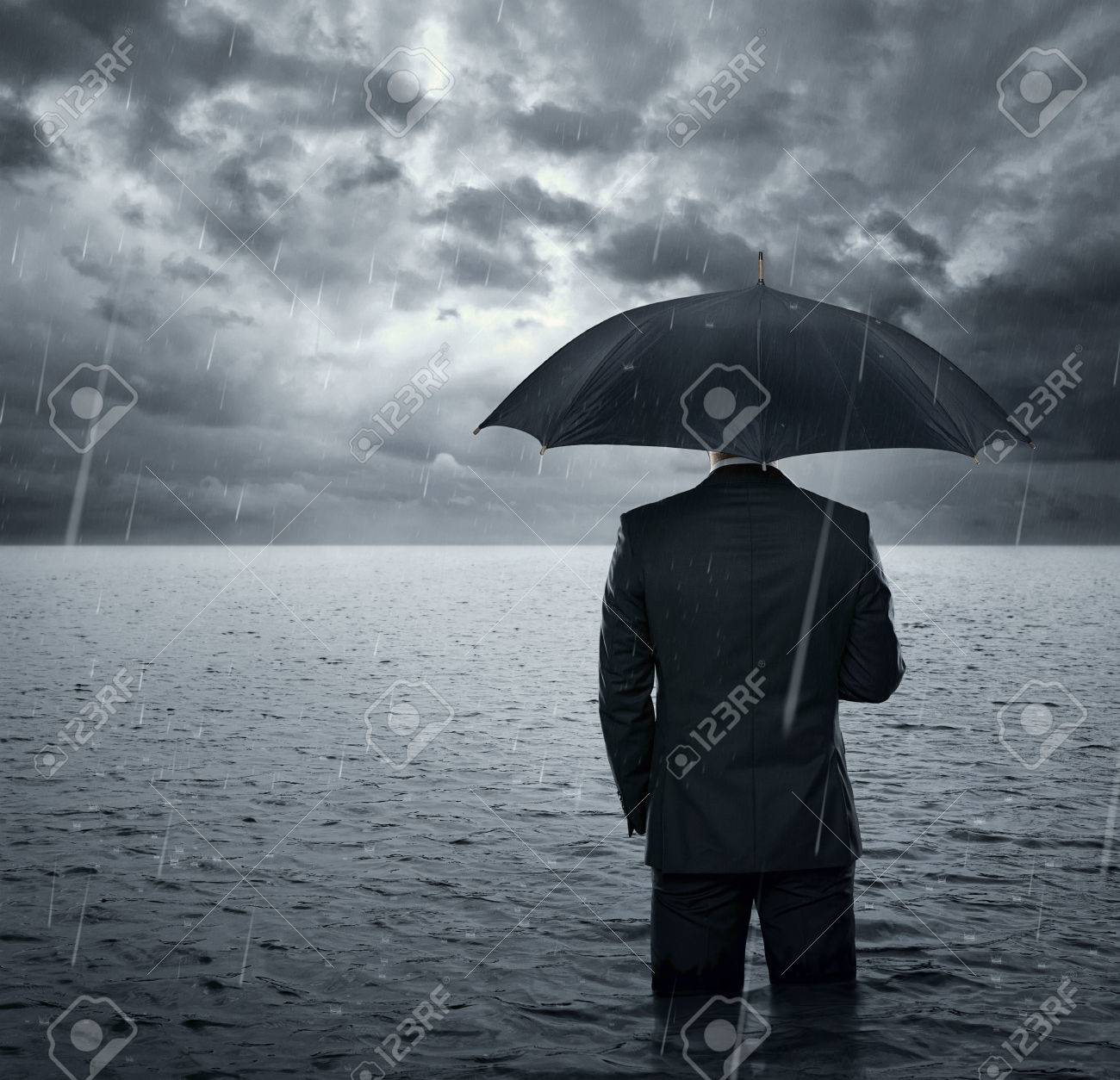 Businessman standing in the dramatic ocean before storm - 23073497
