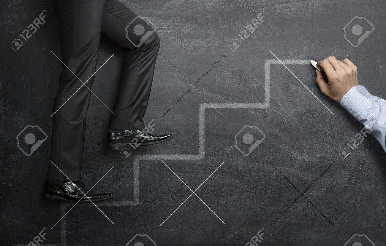 Businessman climbing the career steps drawn on a black chalkboard - 25305294