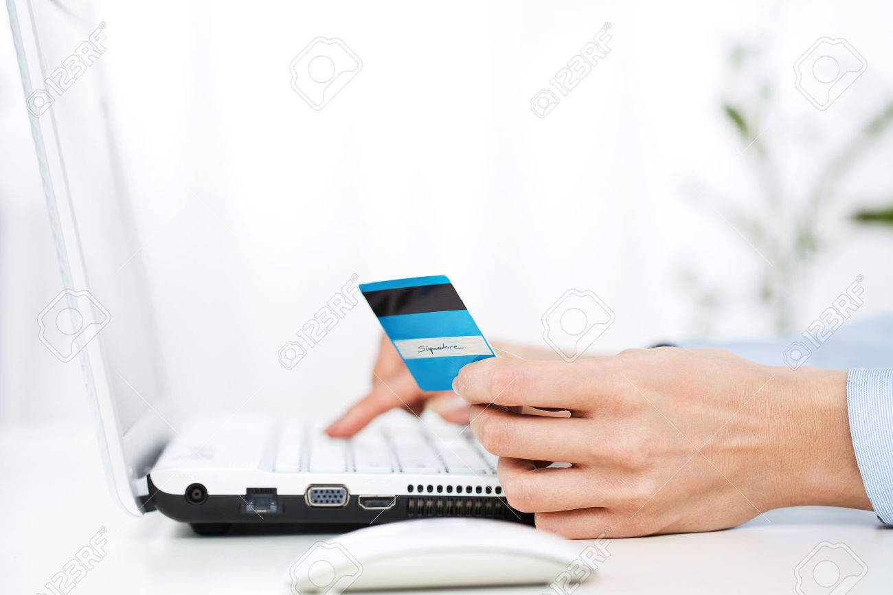 Close up of young woman using credit card - 25305448