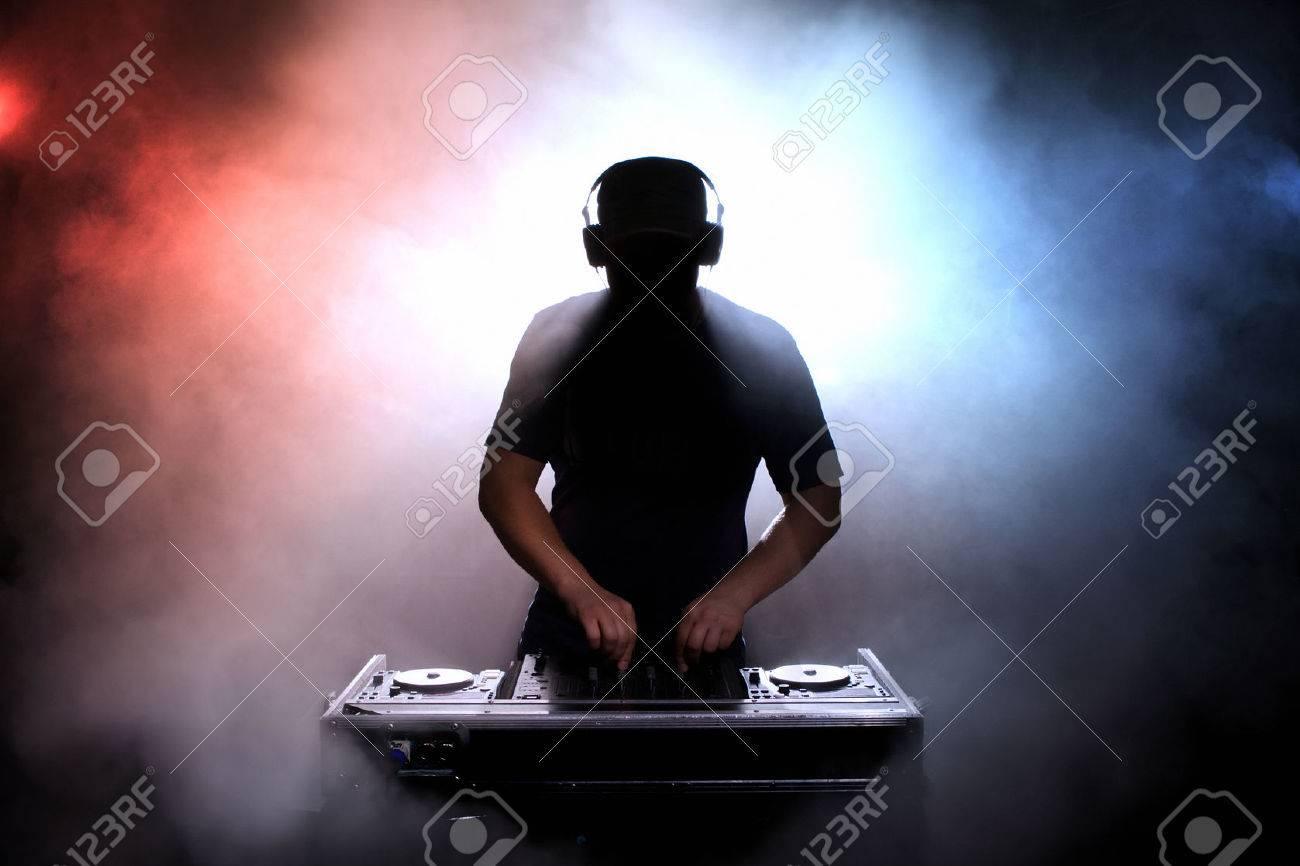 Disc jokey silhouette over illuminated smoke background - 26822753