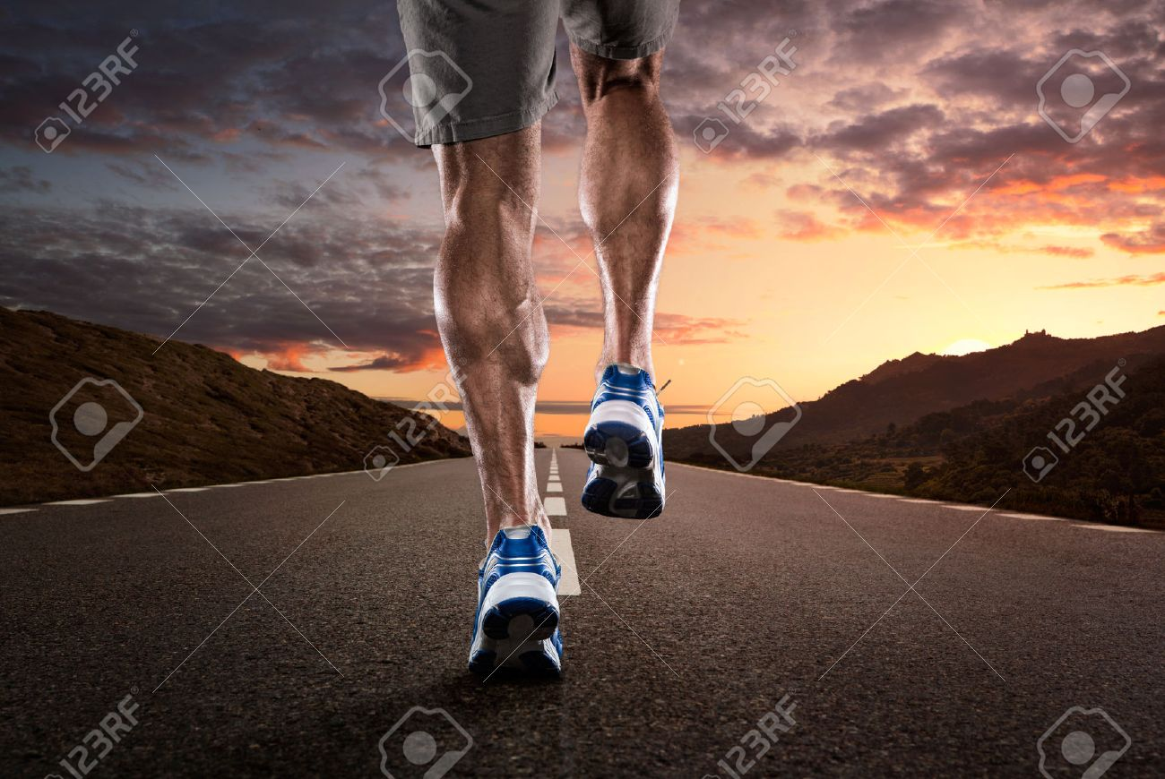 Close up of athlete running on the empty road at the sunset - 31399850