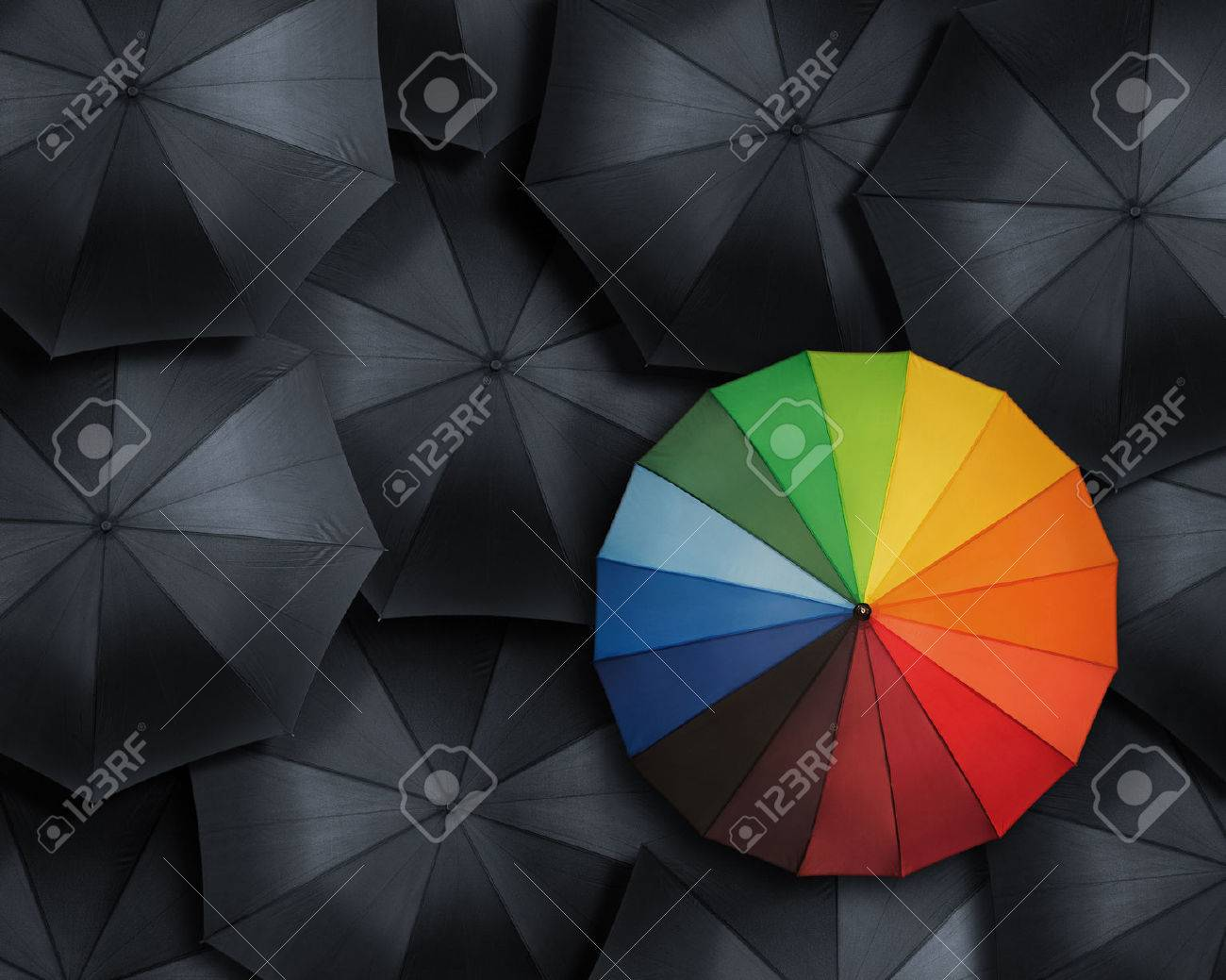 Standing out from the crowd, high angle view of colorful umbrella over many black ones - 31475656