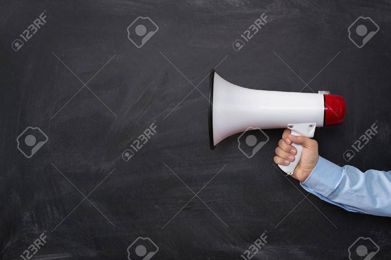 Close up of businessmans hand holding megaphone over dark background with copy space - 33754476