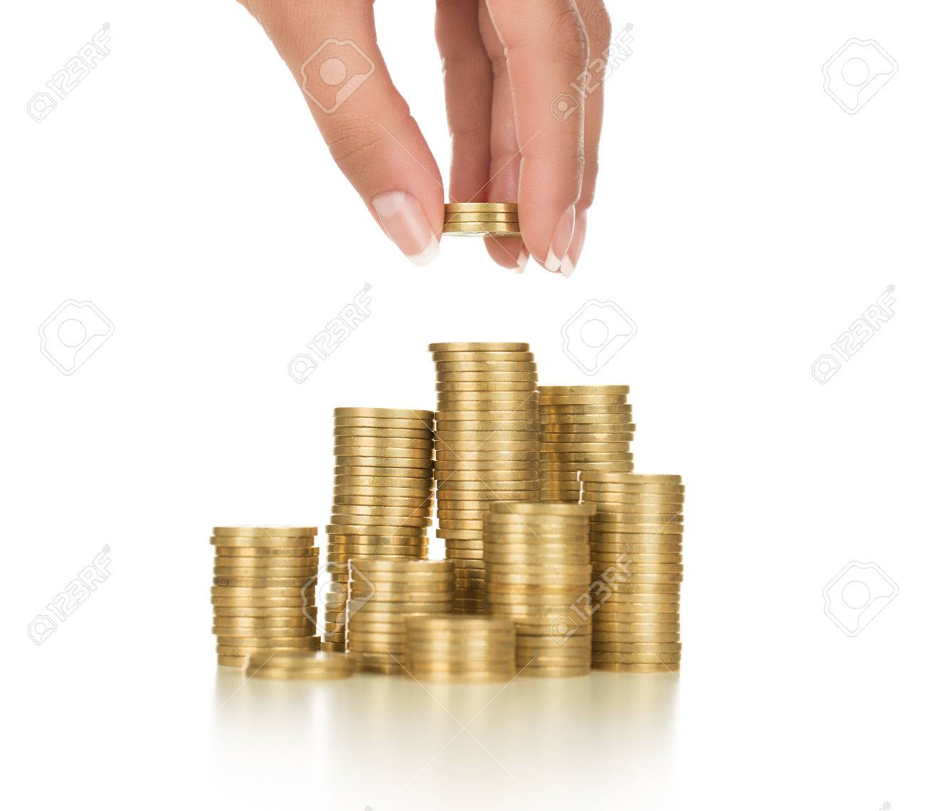 Close up of female hand stacking gold coins isolated on white background - 35119651