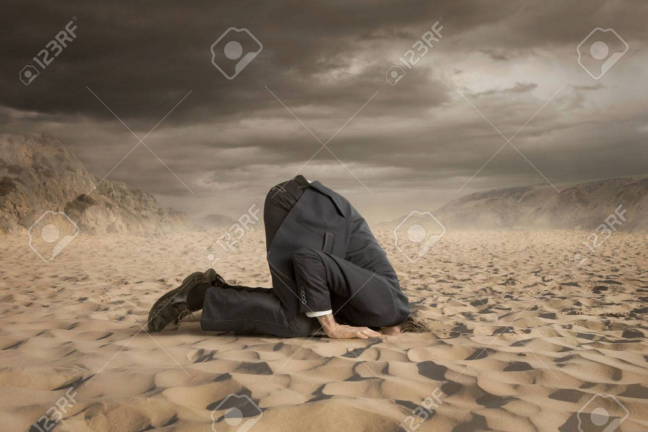 Young businessman hiding head in the sand - 42776058