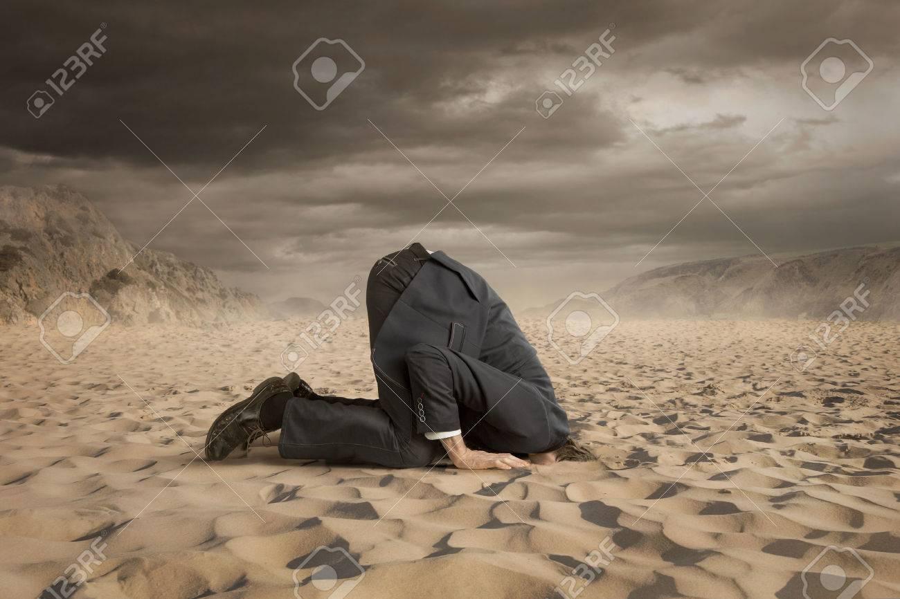 Junger Geschäftsmann versteckt Kopf in den Sand Standard-Bild - 42776058