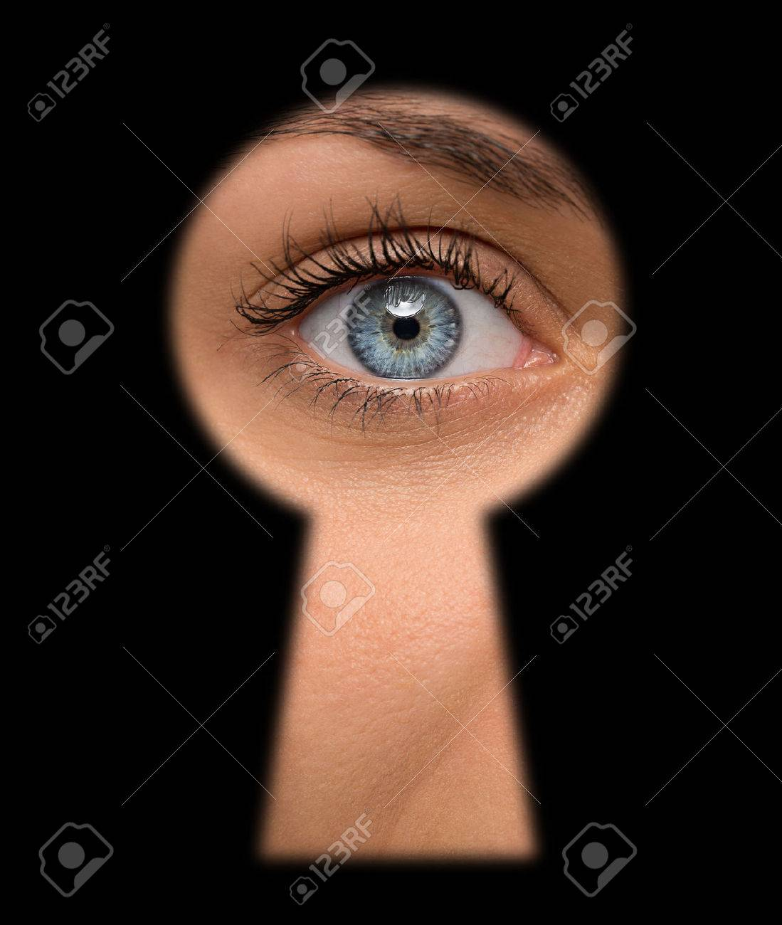 Close up of shocked female eye looking through a keyhole - 43608544