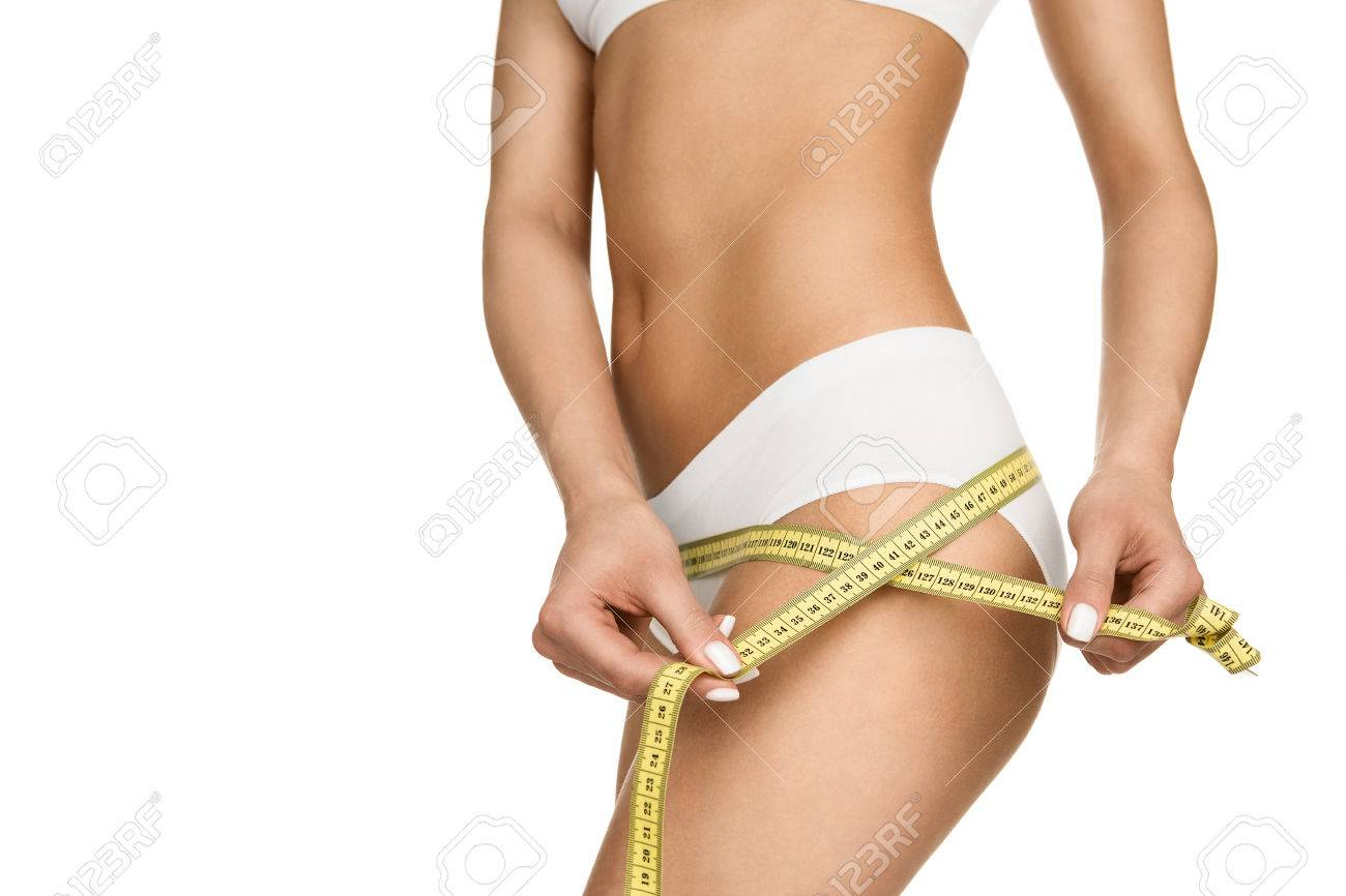 Close up of a slim woman measuring her hips isolated on white background Stock Photo - 44588510