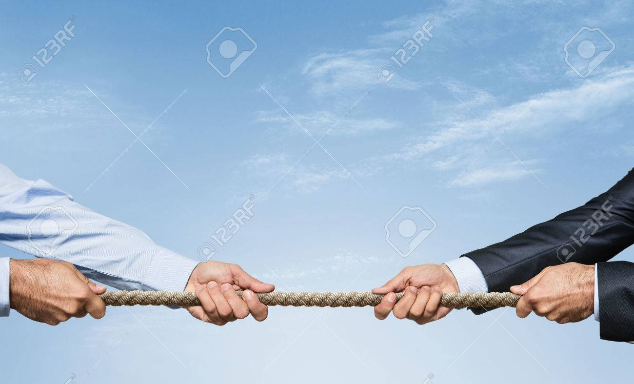 Tug war, two businessman pulling a rope in opposite directions over sky background with copy space Standard-Bild - 50501057