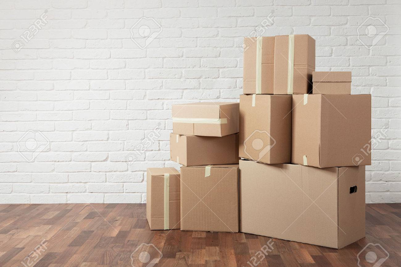 Moving in. Stack of cardboard boxes in the empty room with copy space Standard-Bild - 61991942