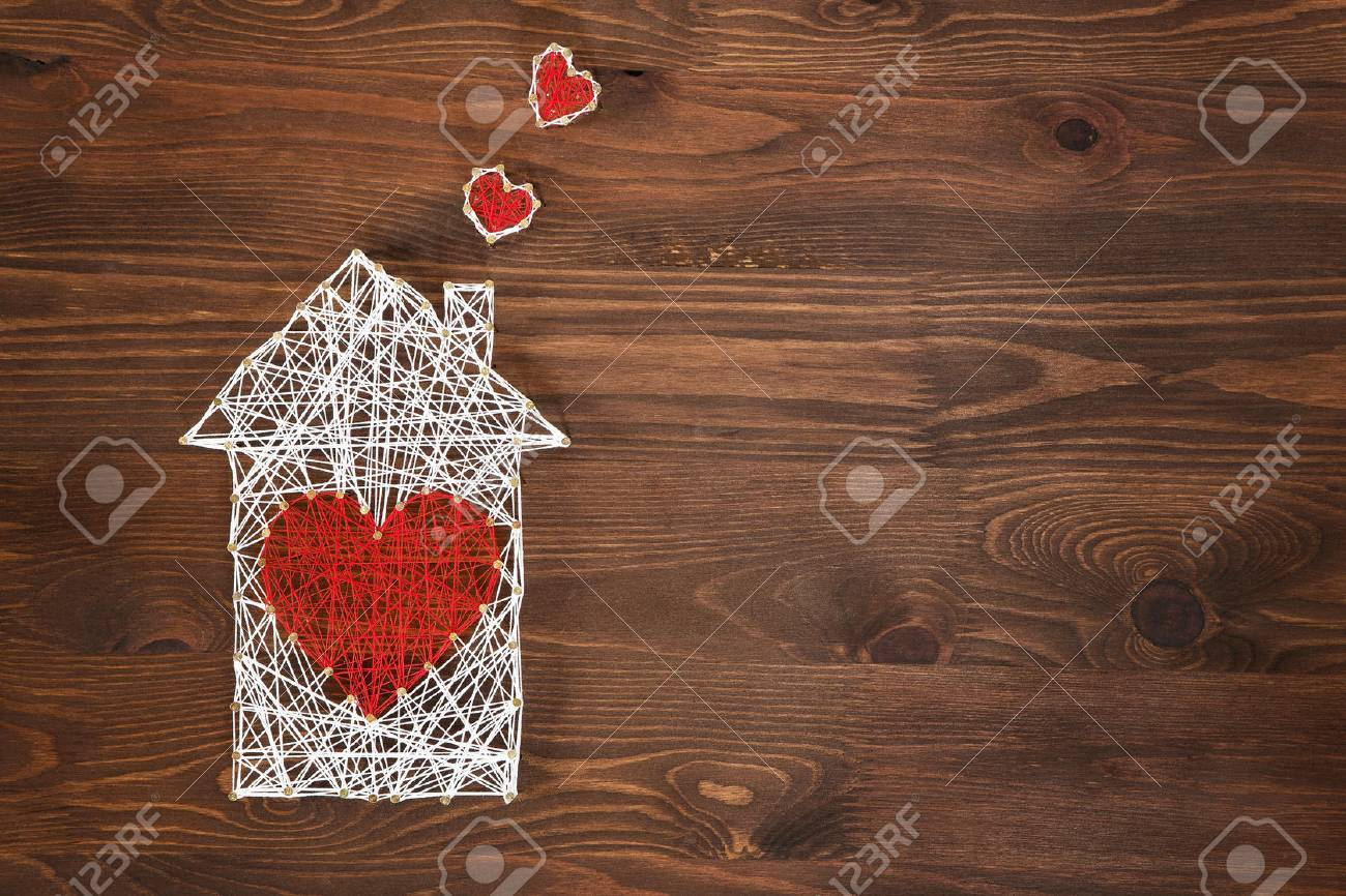 Home sweet home. Handmade home symbol with heart shape on wooden background with copy space Standard-Bild - 70753475