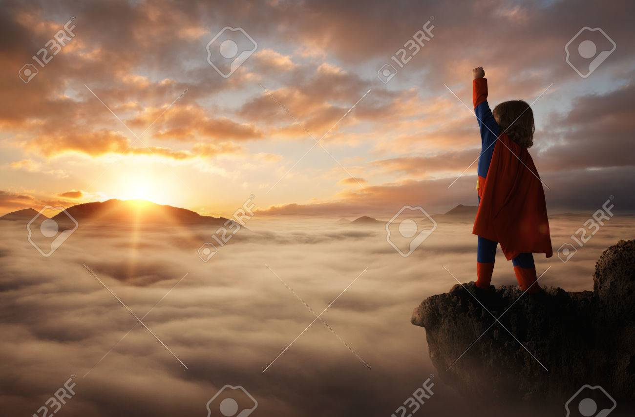 Little boy acting like a superhero on top of the mountain at sunset with copy space - 72765273