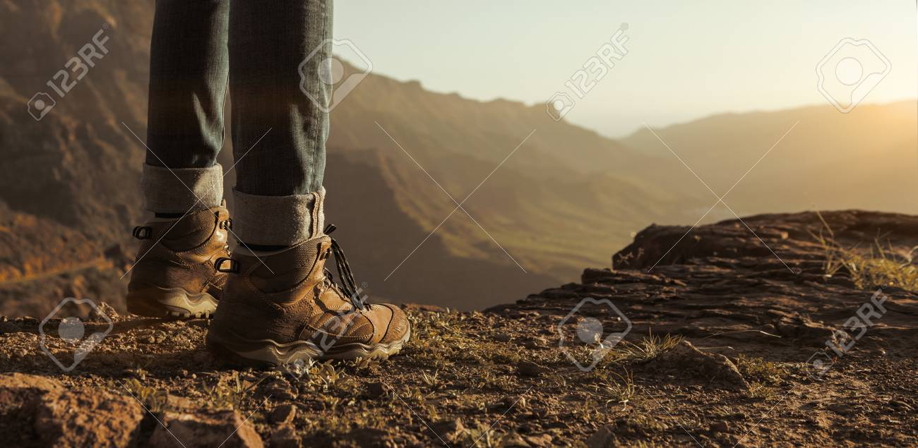 Close up of hikers boots enjoying the sunset in the mountains with copy space - 101770825