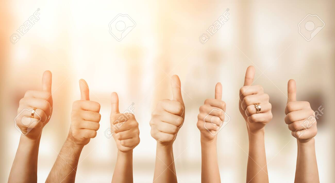 Close up of group of hands showing thumbs up over defocused background with copy space - 130990312