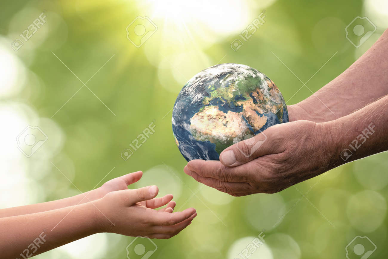 Close up of senior hands giving small planet earth to a child over defocused green background with copy space - 165211735