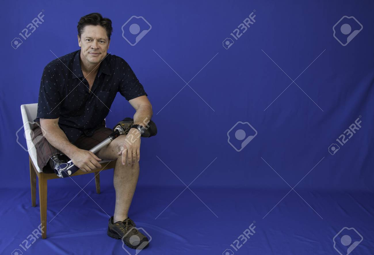Middle-aged man with physical disability, happy with life sitting on the chair - 95534447