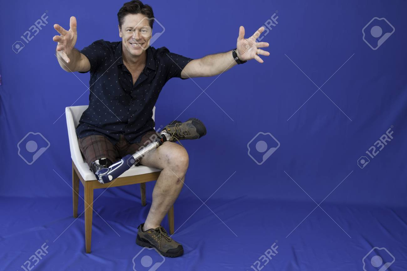 Middle-aged man with physical disability, happy with life sitting on the chair - 95656233
