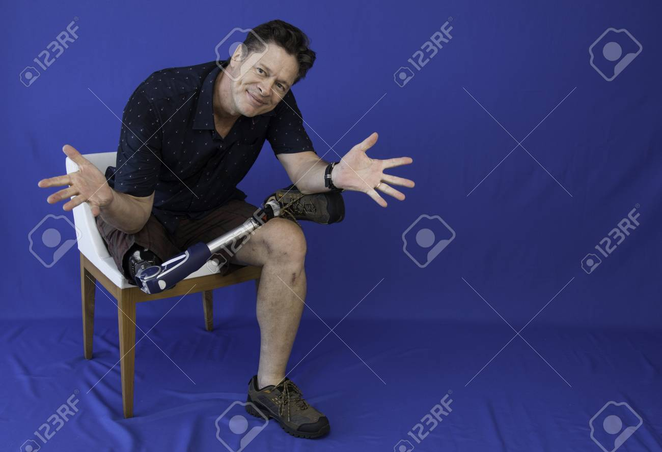 Middle-aged man with physical disability, happy with life sitting on the chair - 95723893