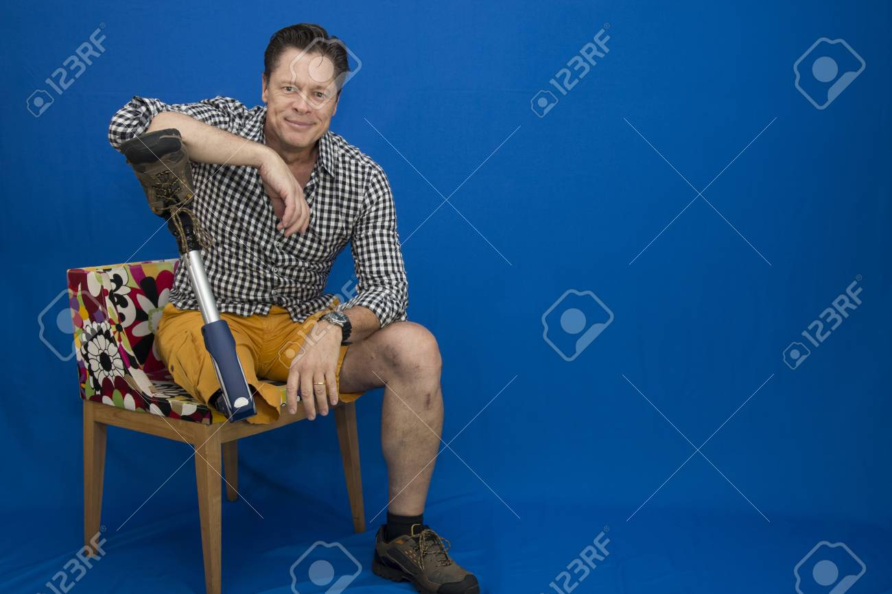 Middle-aged man with physical disability, happy with life sitting on the chair - 96380831
