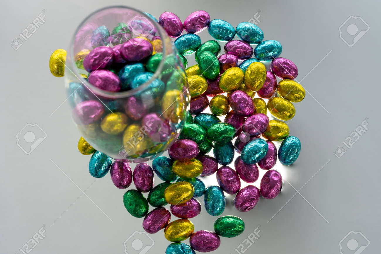 Many colors together. Glass vase with chocolate candies. - 166965969