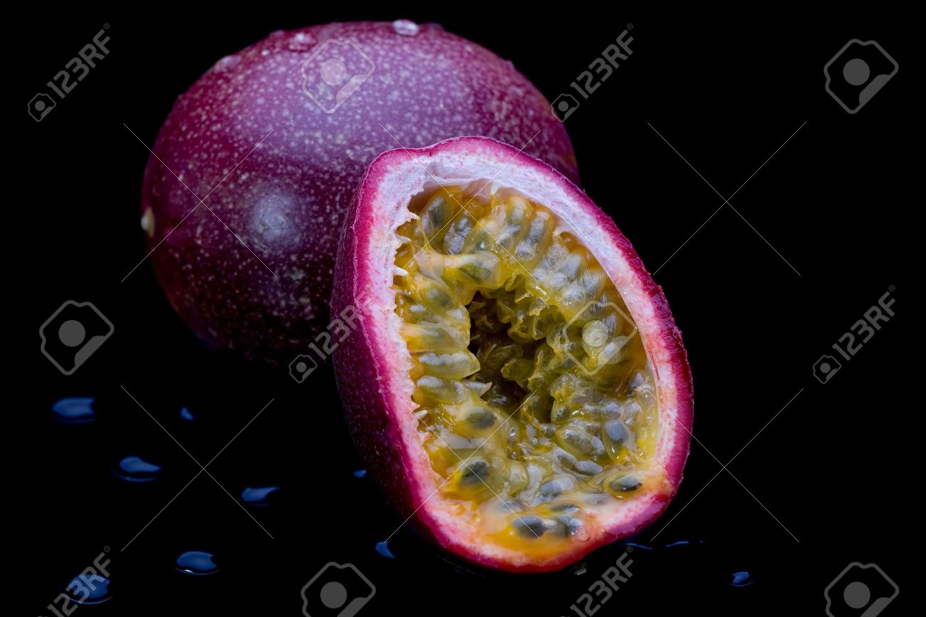 Whole and sliced passion fruit on black background with water droplets. Stock Photo - 8110604