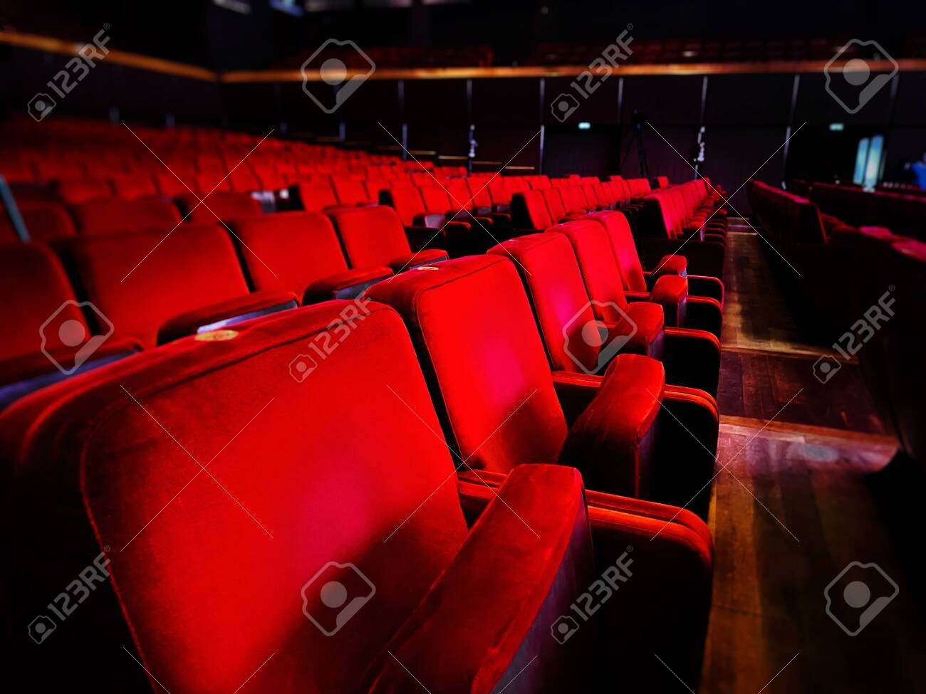 a row of empty red velvet armchairs inside an auditorium. Interior of a theater or cinema - 143595938