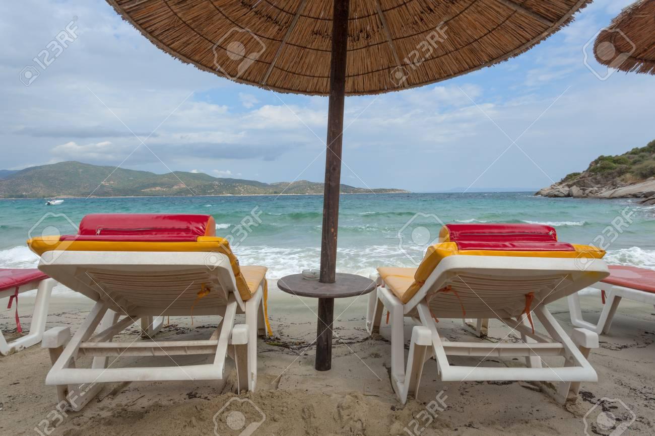 Due sedie a sdraio e ombrellone di paglia sulla riva in giornata