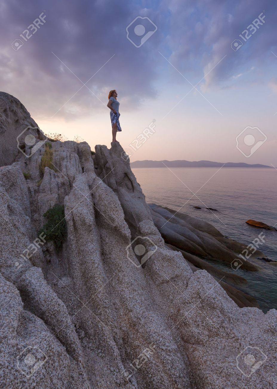 Lone woman standing on an edge of cliff and watching the setting sun from the shore with strange rocks. Coastline of Aegean Sea, Greece. - 60945324