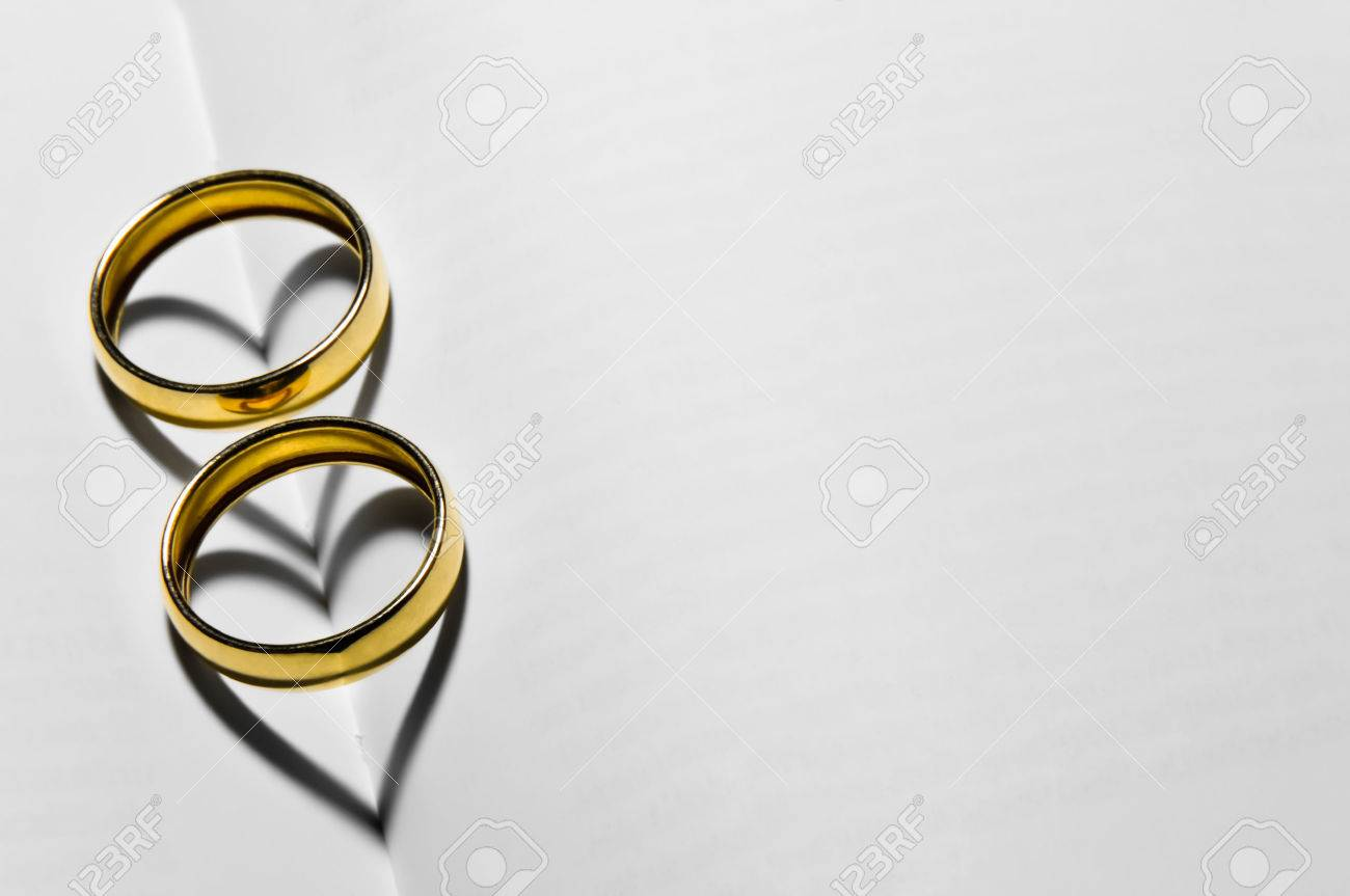 Two Wedding Rings On Top Of The Blank Pages That Form Hearts With Their Shadows
