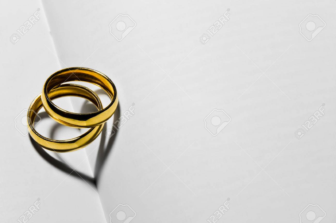 Close up of two wedding rings that create two hearts in heir shadow - 51791899