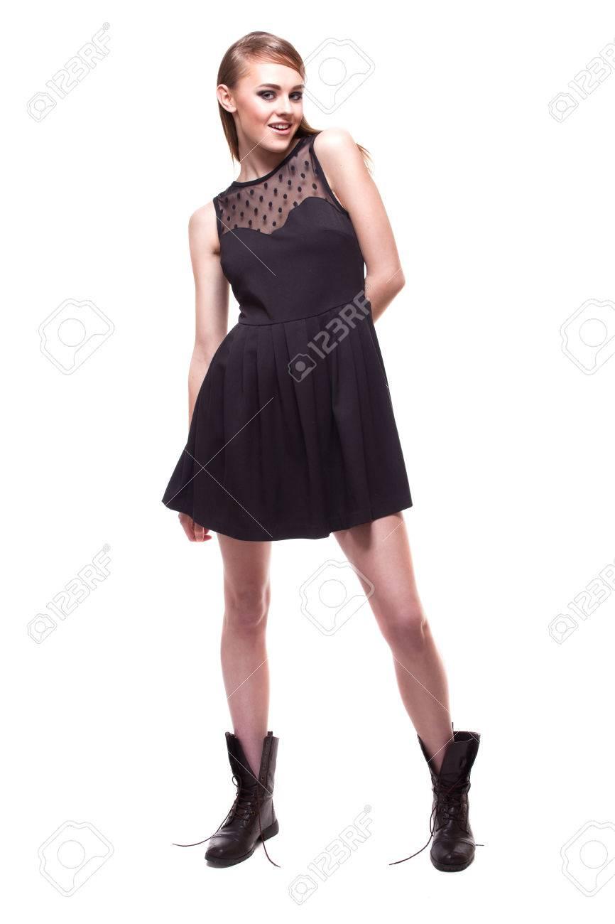 Retrato De Todo El Crecimiento De La Niña En El Vestido Negro Y Botas Sobre Blanco