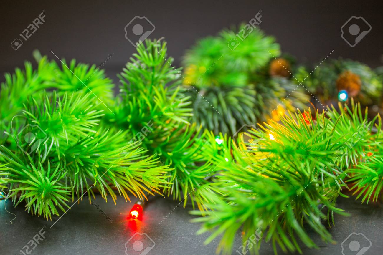 fir branches with christmas multi colored garland on a black background stock photo 66445481