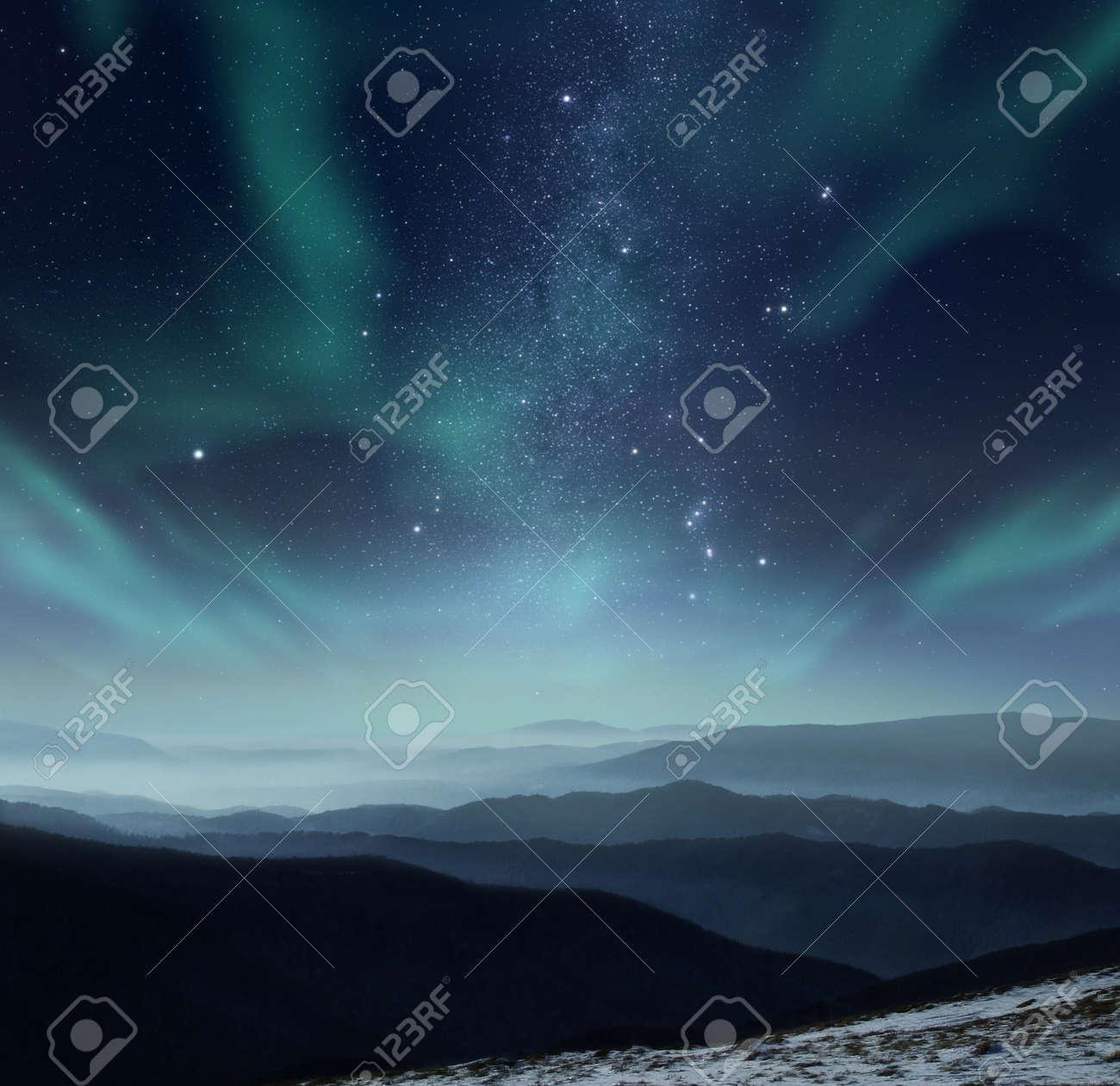 Starry night sky with aurora polaris over the mountains - 58768004
