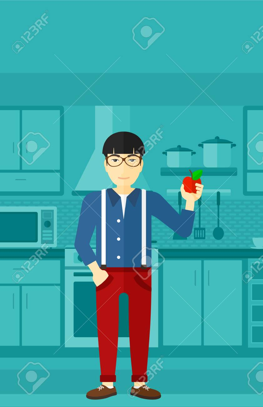 An Asian Man Standing In The Kitchen And Holding An Apple In ...