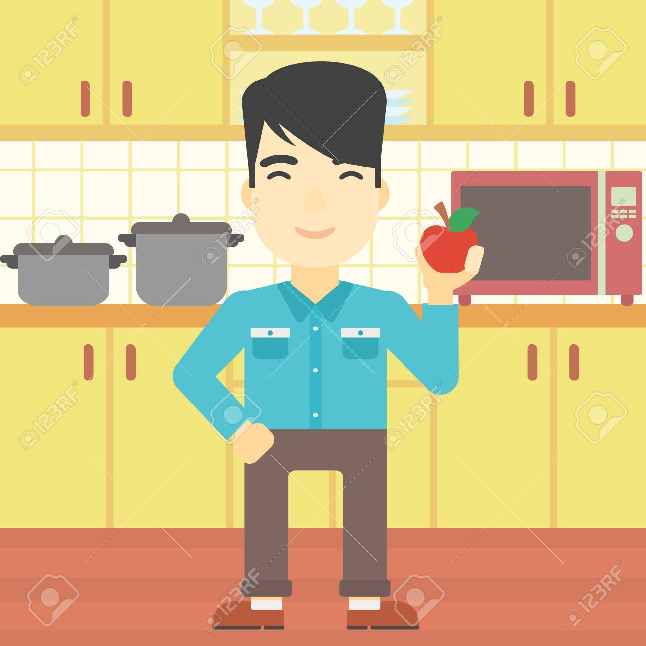An Asian Man Holding An Apple In The Kitchen. Young Man Eating ...