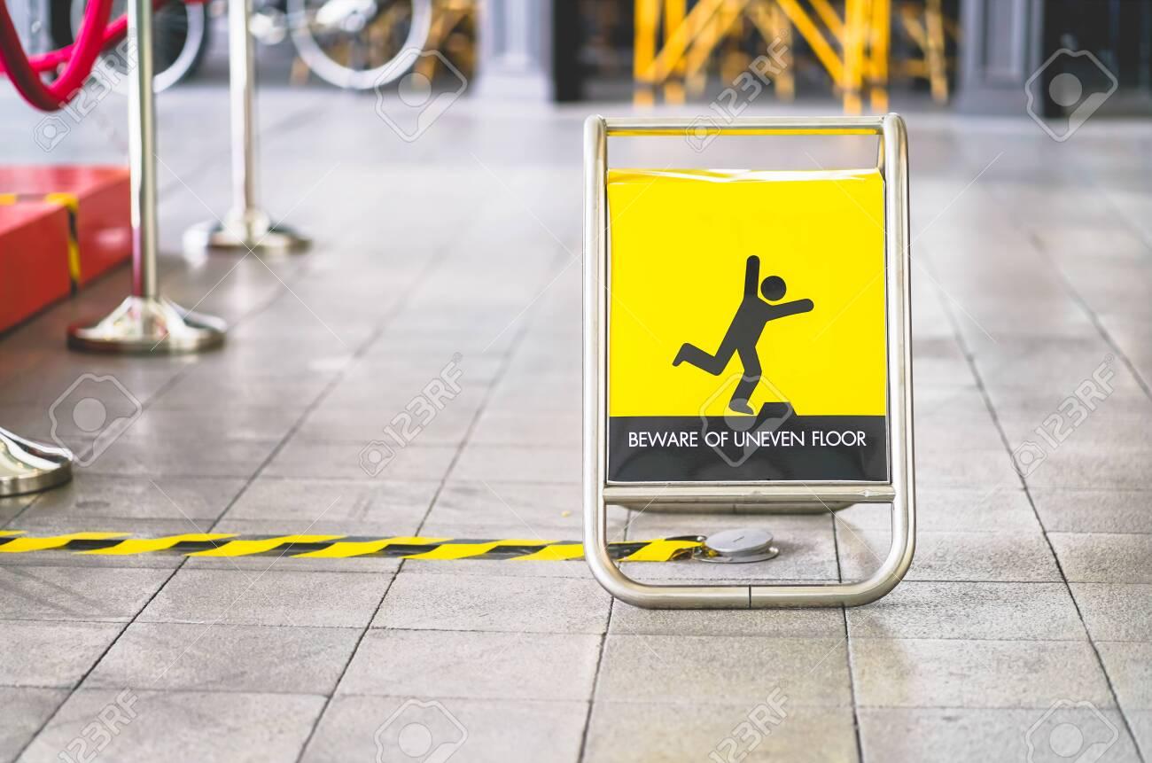 yellow beware of uneven floor sign board on tile floor - 131534142
