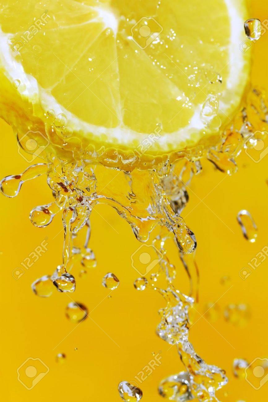 Fresh slice of lemon and water splash on an orange surface - 12405223
