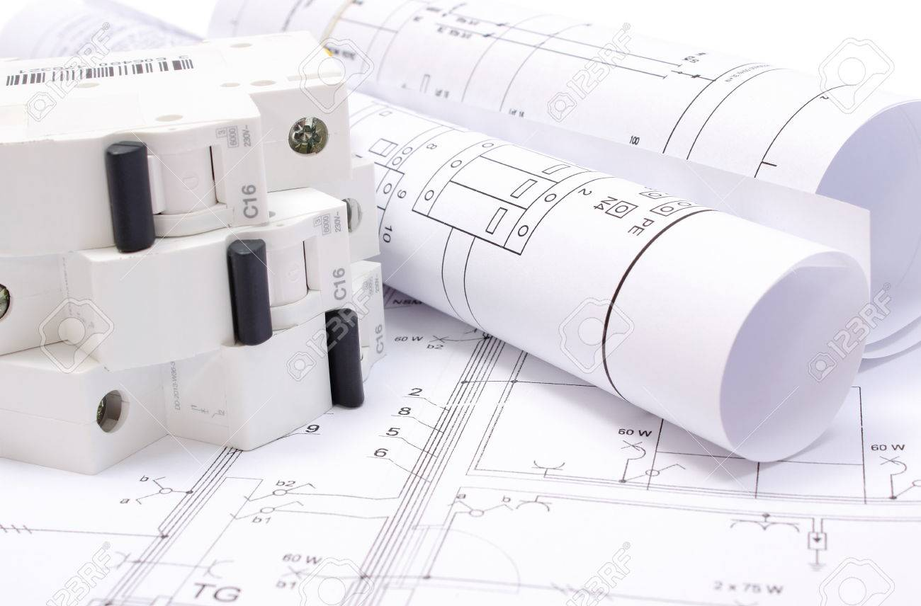 rolled electrical diagrams and electric fuse lying on construction drawing of house drawings for the