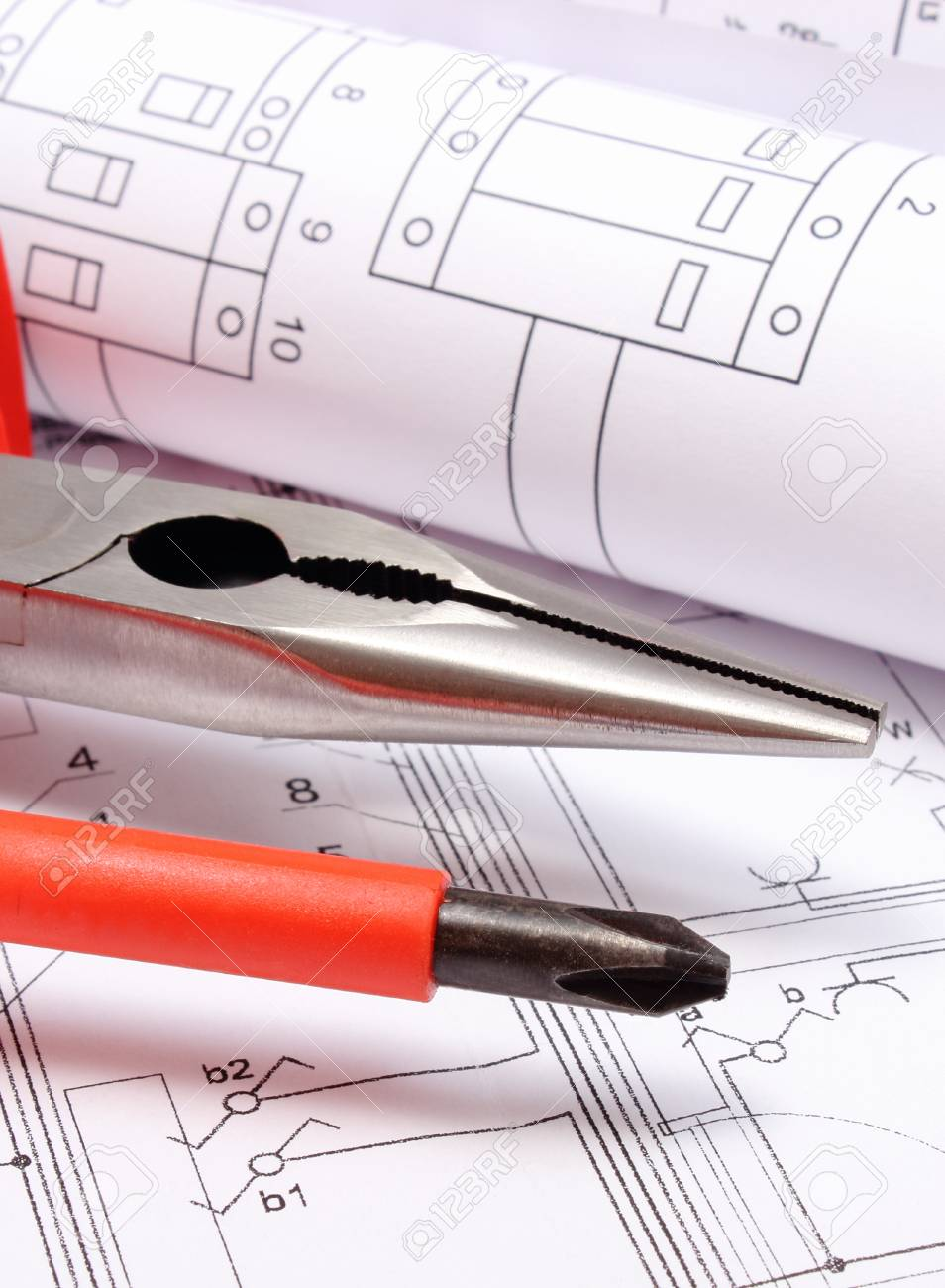 rolled electrical diagrams with work tools lying on construction drawing of house drawings for the