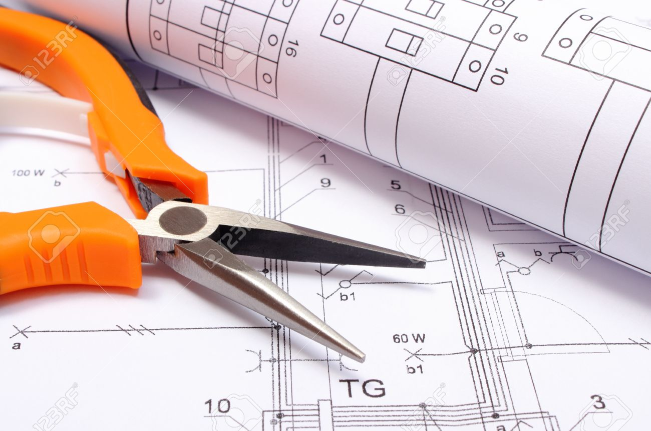 orange metal pliers with rolled electrical diagram lying on construction drawing of house work tool