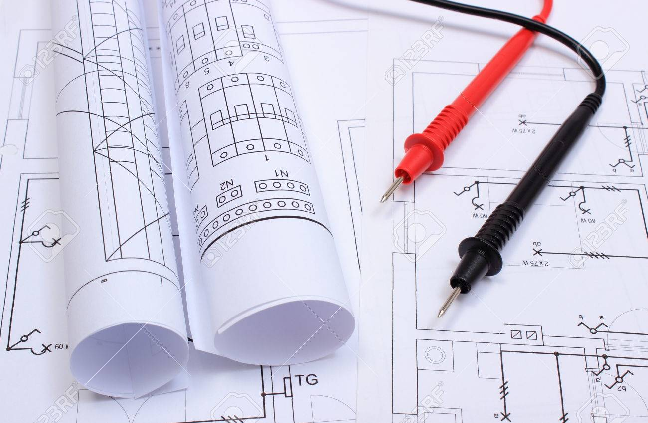 rolls of electrical diagrams and cables of multimeter lying on construction drawing of house drawings